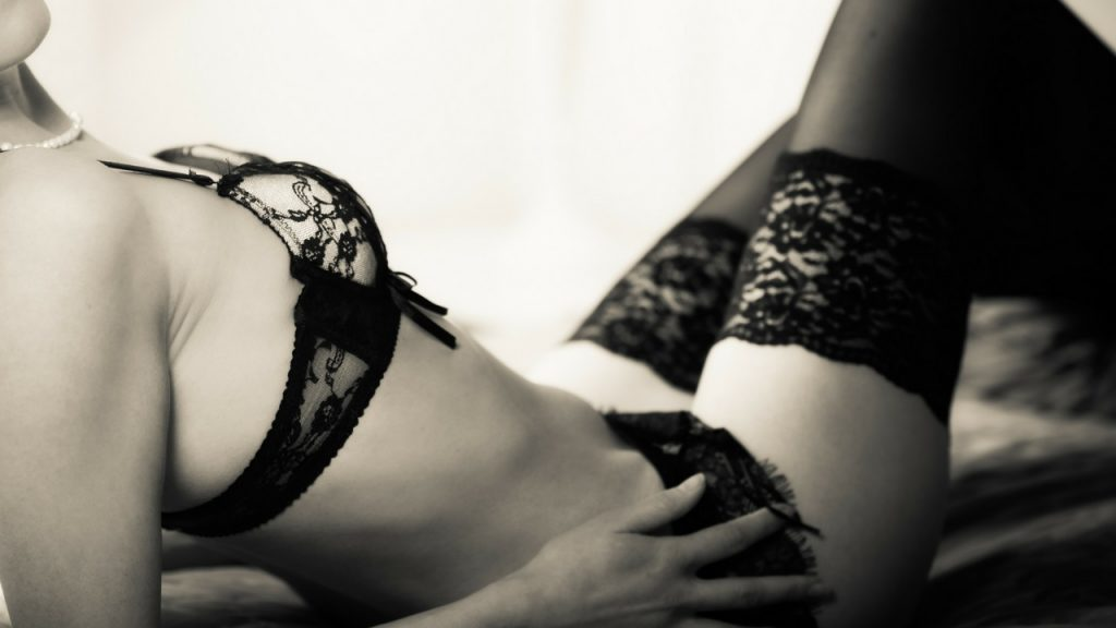 black and white image of a woman in black lace lingerie set with stockings