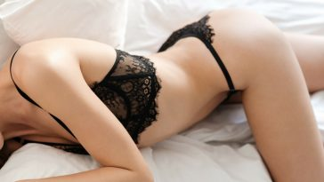 woman laying on bed in black underwear