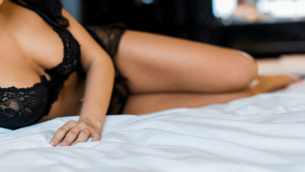 woman in black lingerie laying on bed