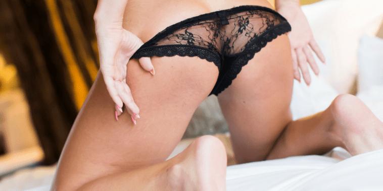 woman in black sexy panties kneeling on bed