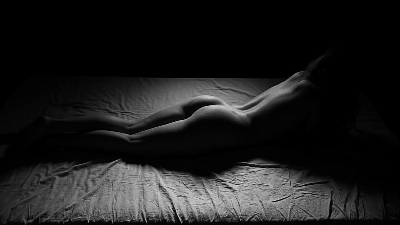Tasteful black and white photo of woman laying on naked bed