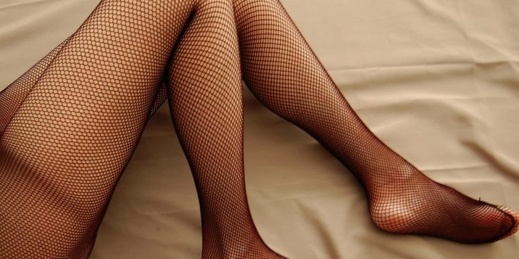 girls legs in stockings laying on bed