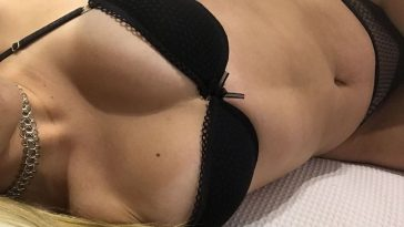 Blonde woman laying on bed in black lingerie