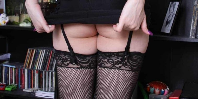 woman standing in front of bookcase in stockings and short skirt